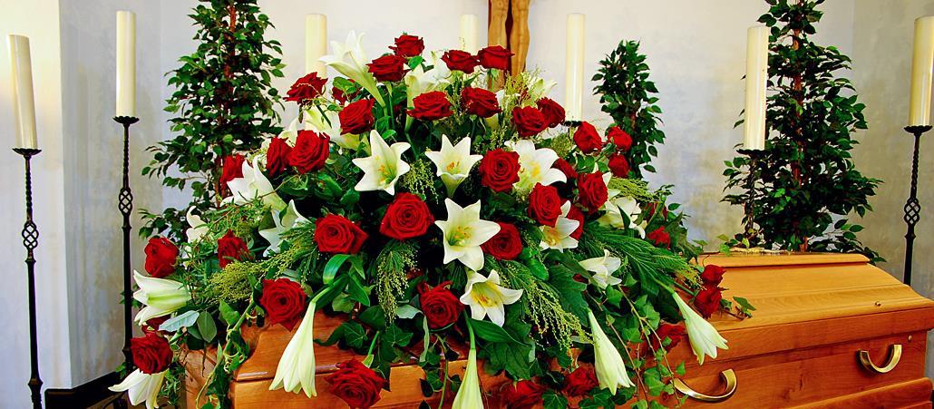 Un ataúd decorado con flores se coloca en la capilla funeraria.