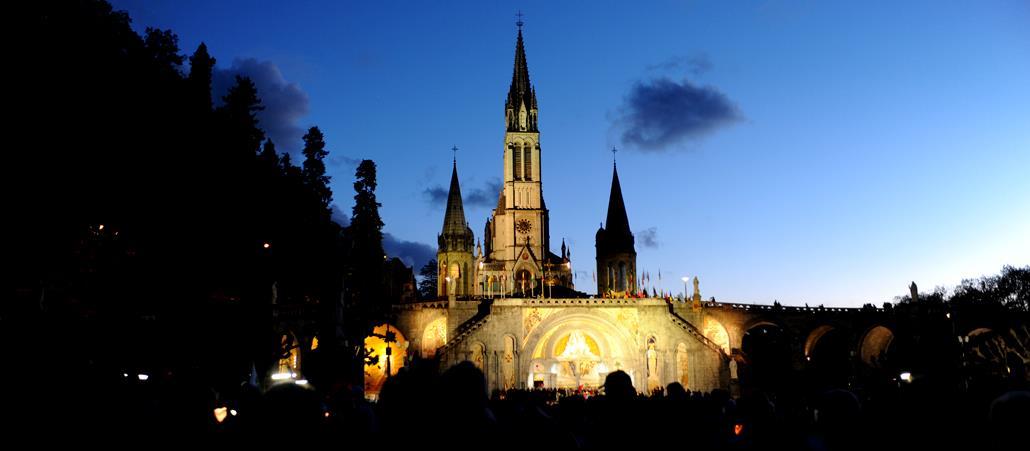 Die beleuchtete Kathedrale hebt sich von dem tiefblauen Abendhimmel ab.
