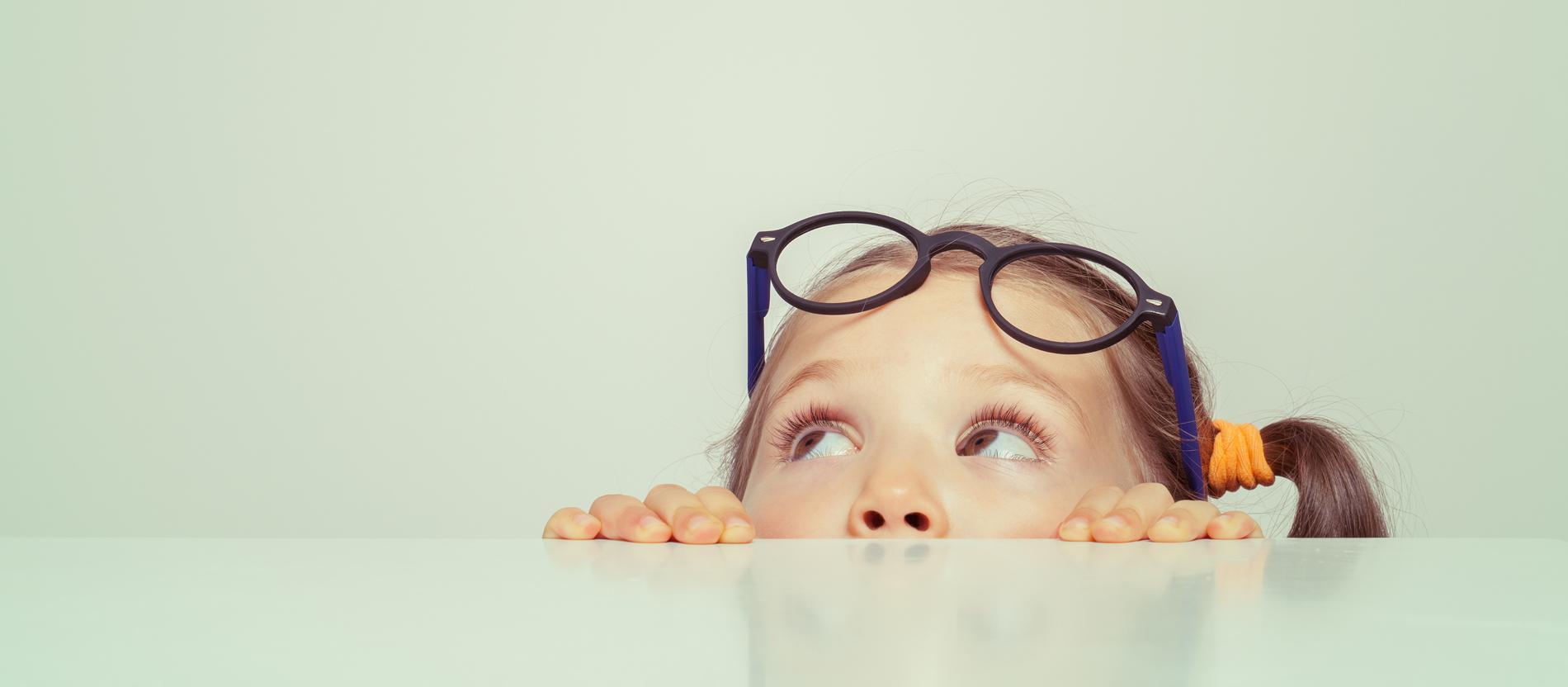 Ein Kind sitzt an einem leeren Tisch und schaut nach oben.