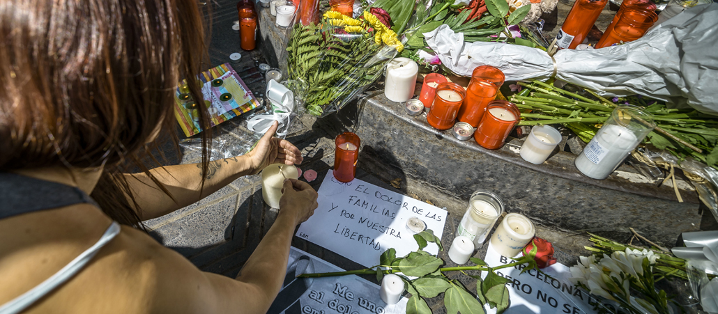 A mourner places a candle at a makeshift memorial at Canaletas Fountains in Las Ramblas